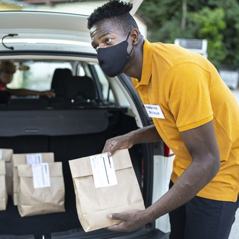 curbside service staff loading shopping bags for customer while staying in car