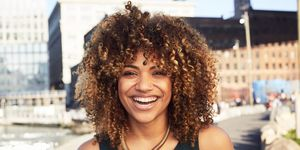 Black woman smiling at waterfront