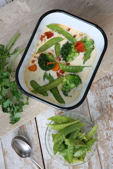 una fuente con verduras variadas como judías verdes, brocoli y zanahoria y una salsa con curry