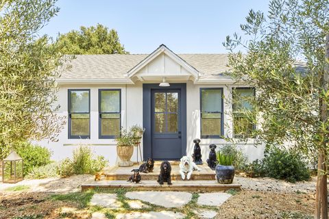 dogs in front of small white cottage with dark gray door
