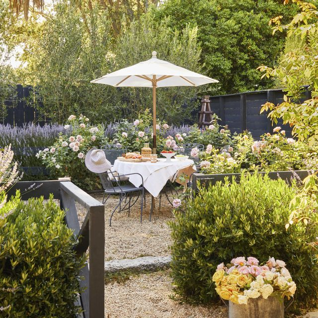 outdoor dining table and chairs in a rose and lavender garden