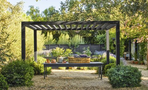 black wood pergola in lavender garden with long table underneath