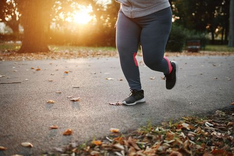 Curvaceous young female runner running in park, waist down