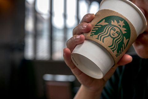Customer drinks coffee in a Starbucks cafe. Starbucks is...