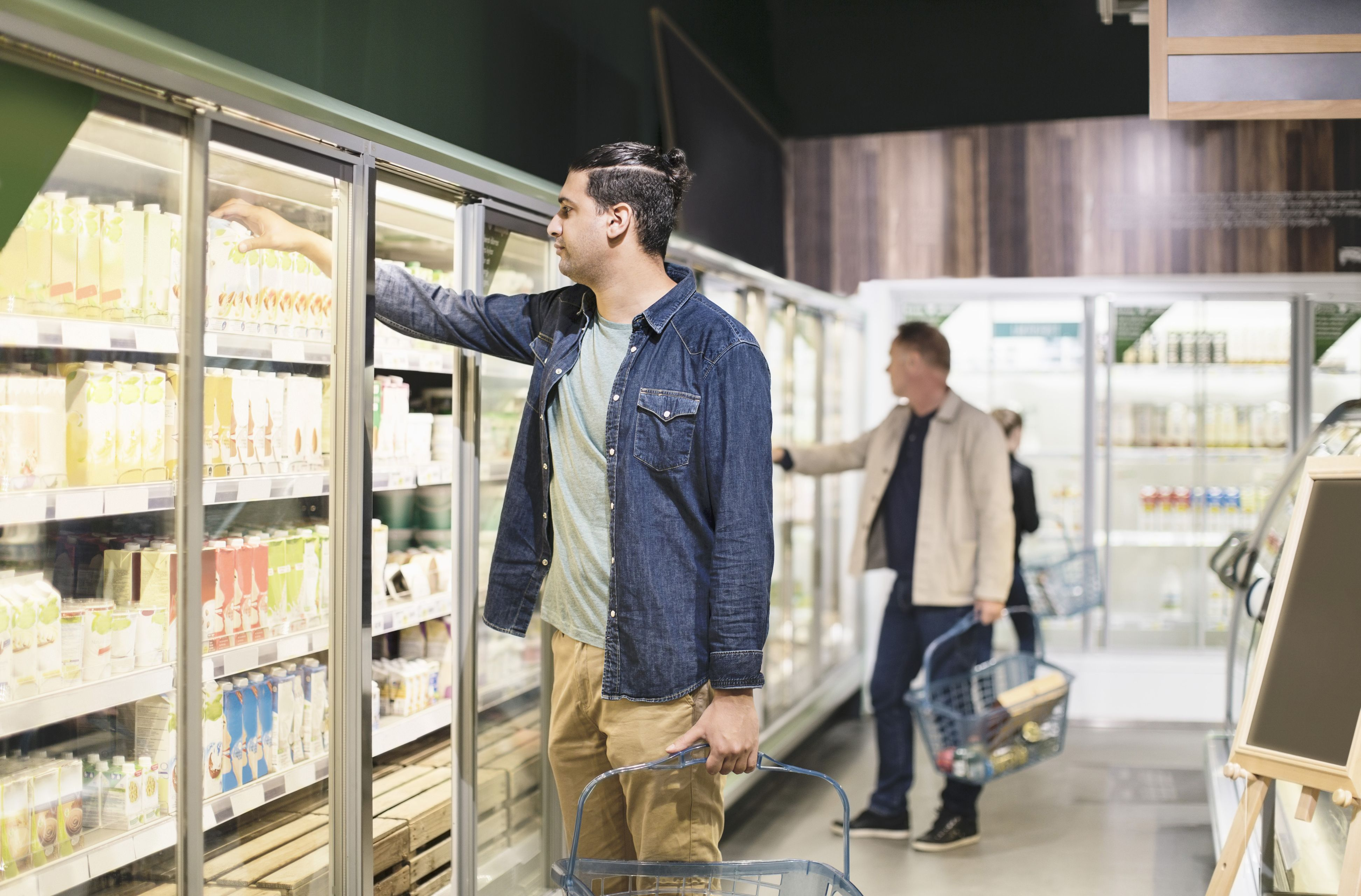 Customers shopping at refrigerated section in supermarket