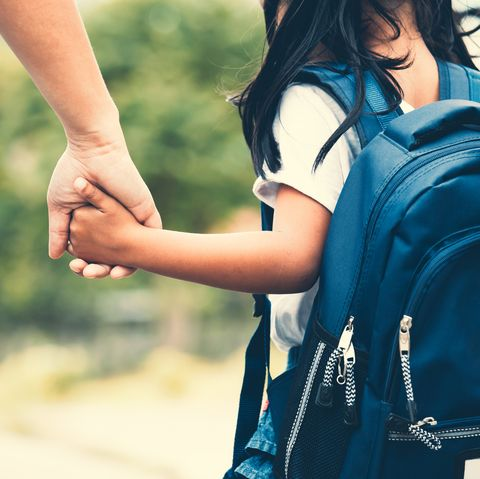 Cute asian pupil girl with backpack holding her mother hand and going to school
