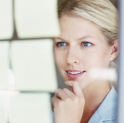 cute business woman reading adhesives notes on glass