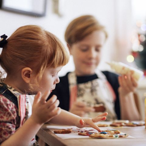 cute girl decorating gingerbread cookies at table