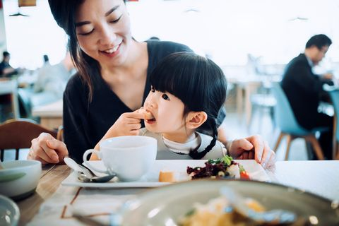 cute little asian girl sitting on her mother's lap and enjoying lunch together in a restaurant