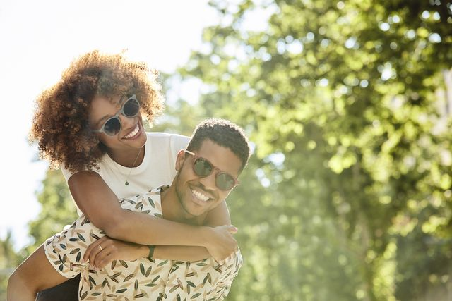 young couple enjoying piggyback ride on sunny day smiling man and woman are spending leisure time in city they are on vacation