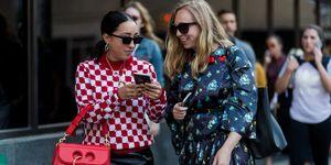 Twee vrouwen op straat kijken op een smartphone