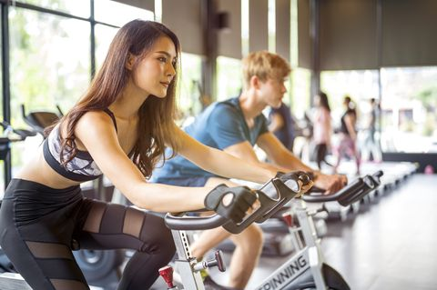 cycling cardio workout young woman and in sportswear cycling at gym