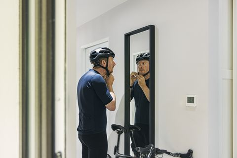 cyclist getting ready he puts his helmet on in the mirror