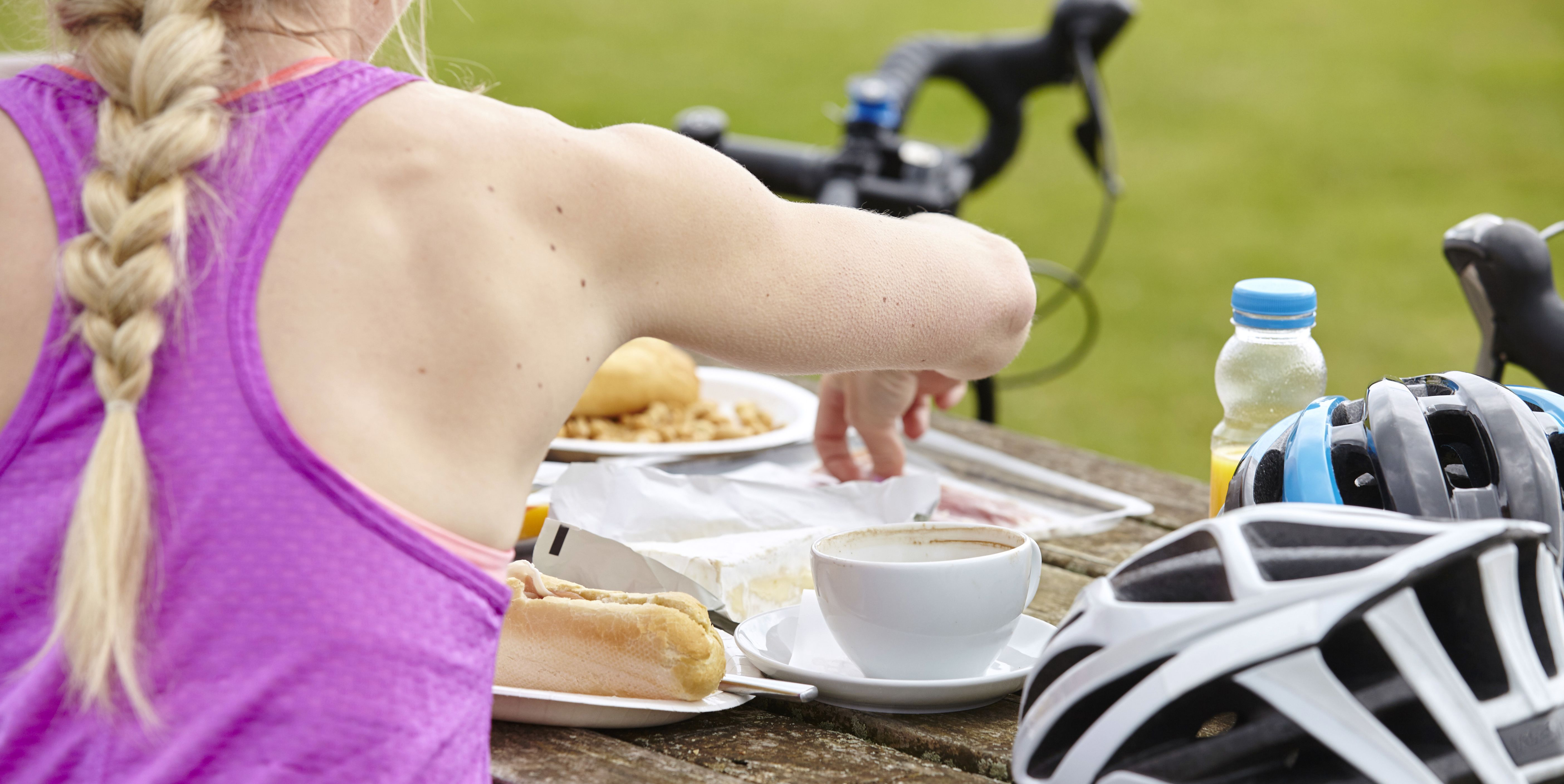 Cyclist having breakfast at picnic table