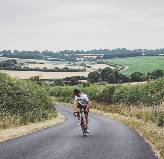 cyclist on country road going uphill