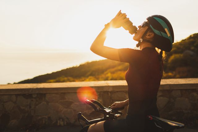cyclist woman taking a break after riding bike and drinking water at sunset