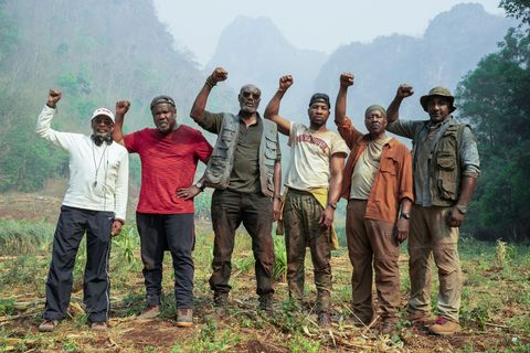 men in jungle with fists raised