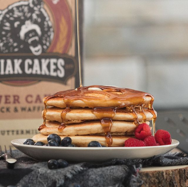 kodiak cakes box in back with stack of pancakes, syrup and fruit
