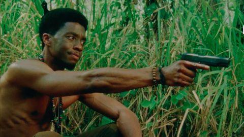 un actor de raza negra apunta con una pistola sin camiseta