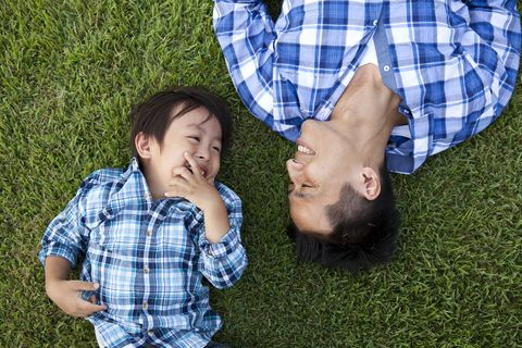 father and son laughing in grass