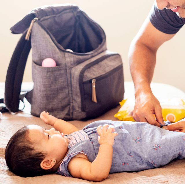 dad changing baby with diaper backpack on bed