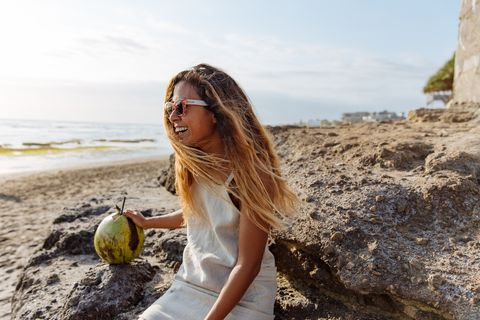 A dark skinned woman sitting at a beach