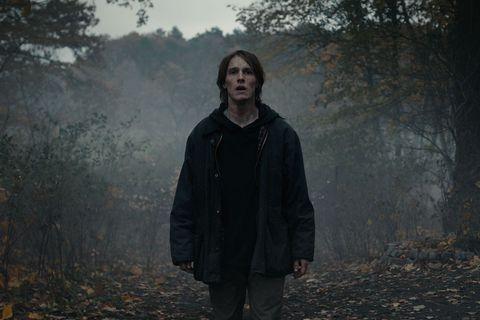un chico camina por un bosque oscuro en dark