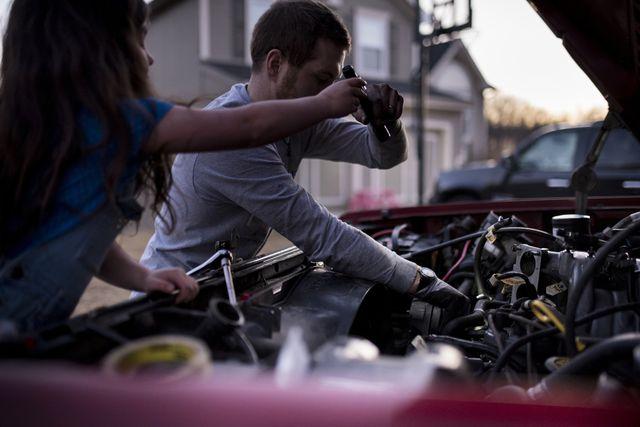 daughter assisting father in repairing car