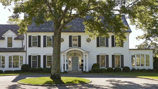 a white colonial style house with black shutters