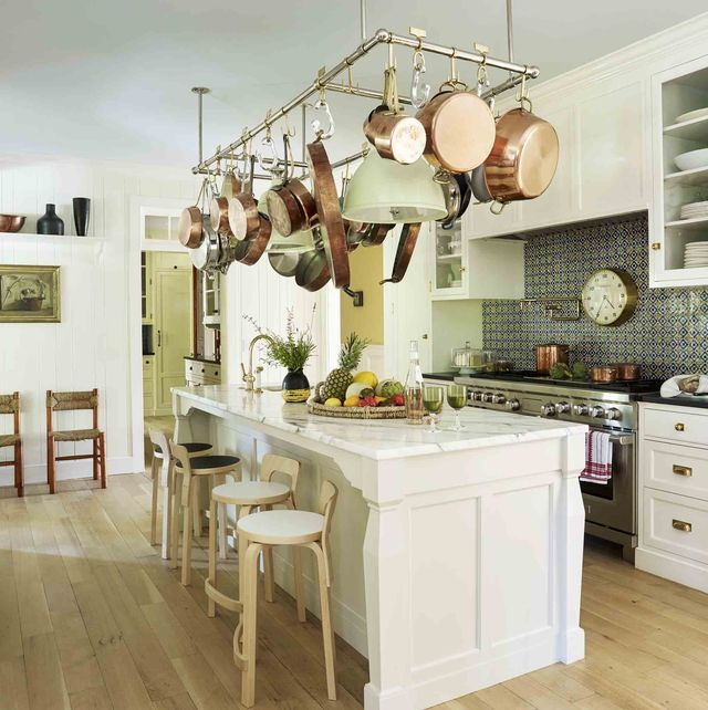 a white kitchen with a large island with a pot rack hanging over it