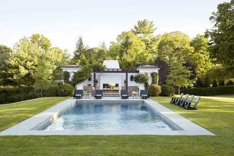 a rectangular pool inset into a lush lawn with a white california style poorhouse int he background