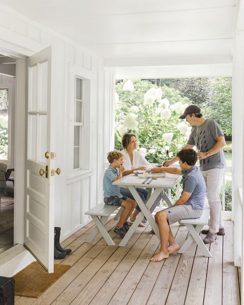 rustic white porch with family sitting at picnic table