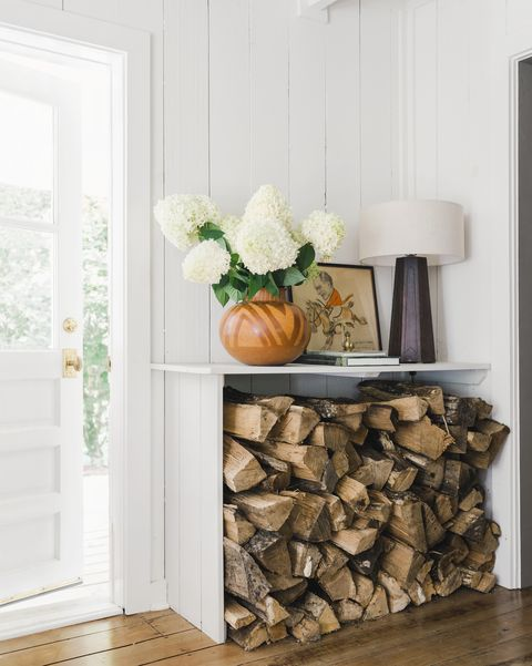 white shelf with wood stacked underneath
