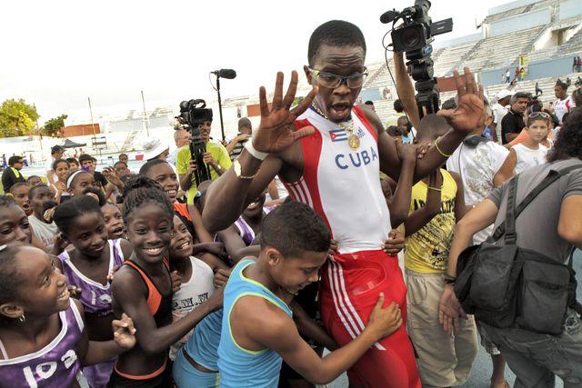 el exatleta cubano dayron robles levanta las manos rodeado de niños en una competición en la habana