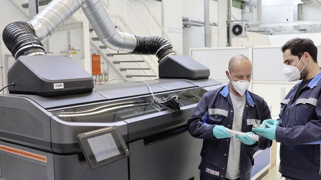 two volkswagen employees check the quality of structural parts produced using the binder jetting process for car production in front of the prototype of the special printer at the high tech 3d printing center in wolfsburg