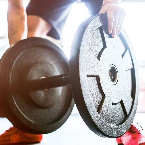 Man Loading Weights to Barbell