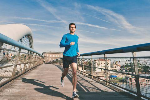 man hardlopen over brug zon