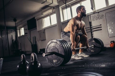 bodybuilder exercising with barbells in the gym