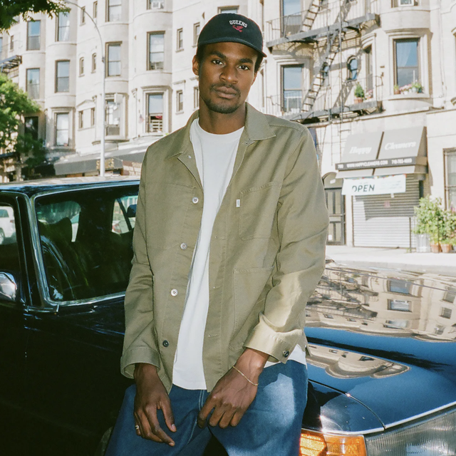 a model sitting on a car wearing a black hat, white t shirt, olive chore coat and blue jeans