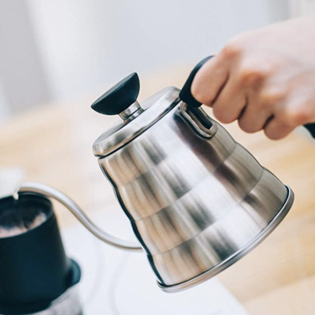 a stainless steel kettle being poured into a mug