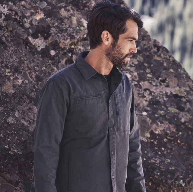 a model in front of a boulder wearing a graphite jacket