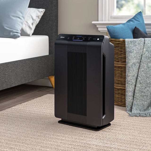 a black air purifier in a bedroom scene