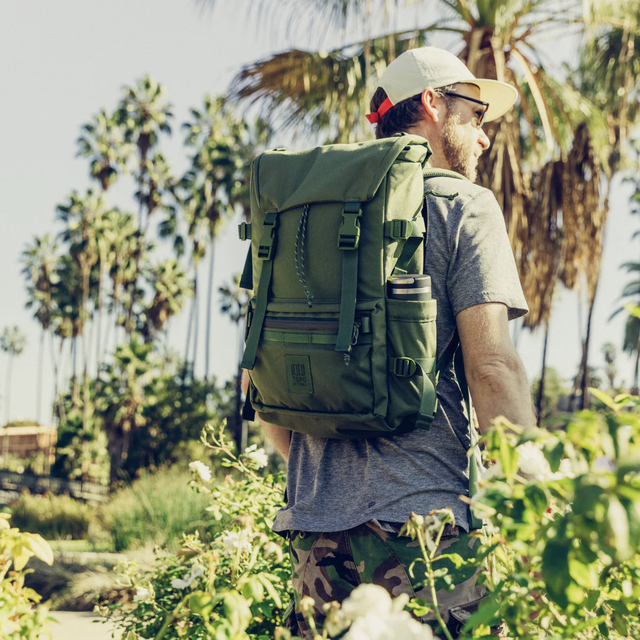 a model with an olive backpack in a jungle