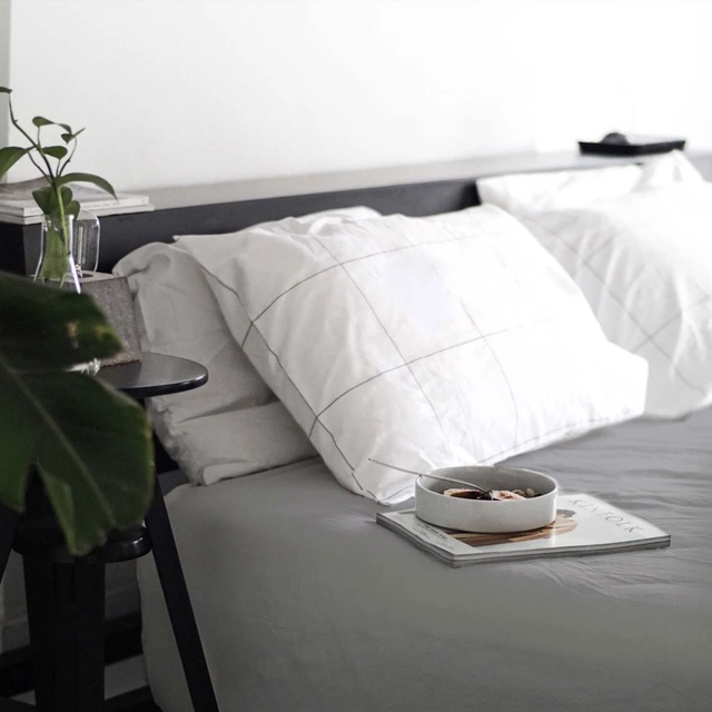 a bed with a gray duvet cover