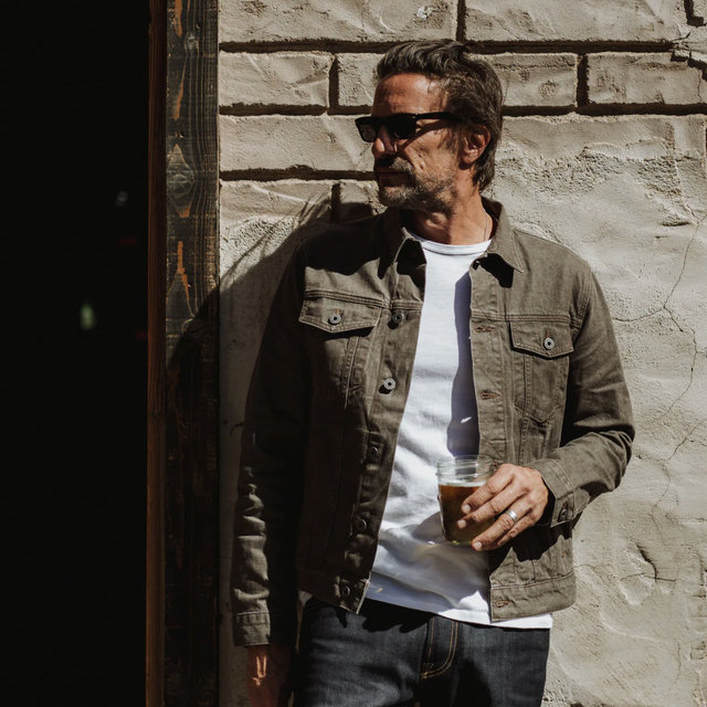 a model wearing a brown denim jacket, white t shirt and blue jeans standing against a wall