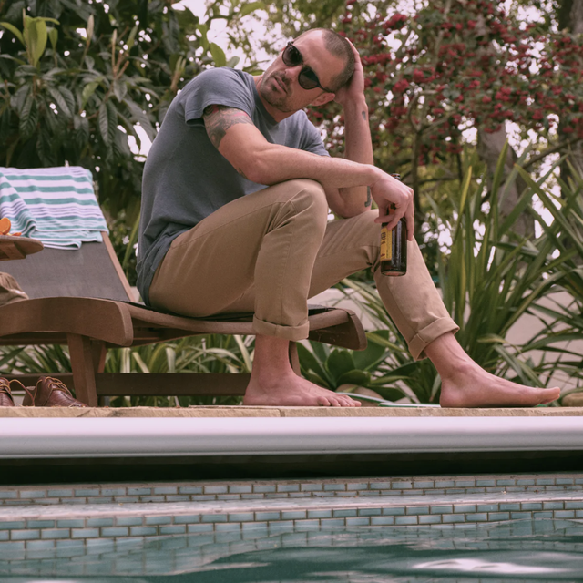 a model sitting by a pool with a beer, khakis and a gray t shirt