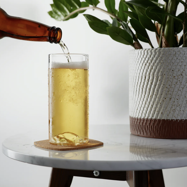 a beer bottle being poured into a beer glass on a table with a plant