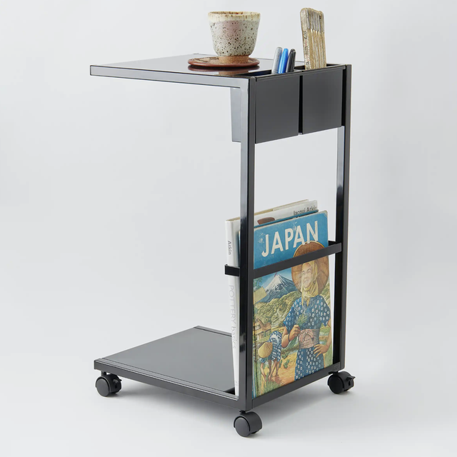 a side table on wheels on a gray background