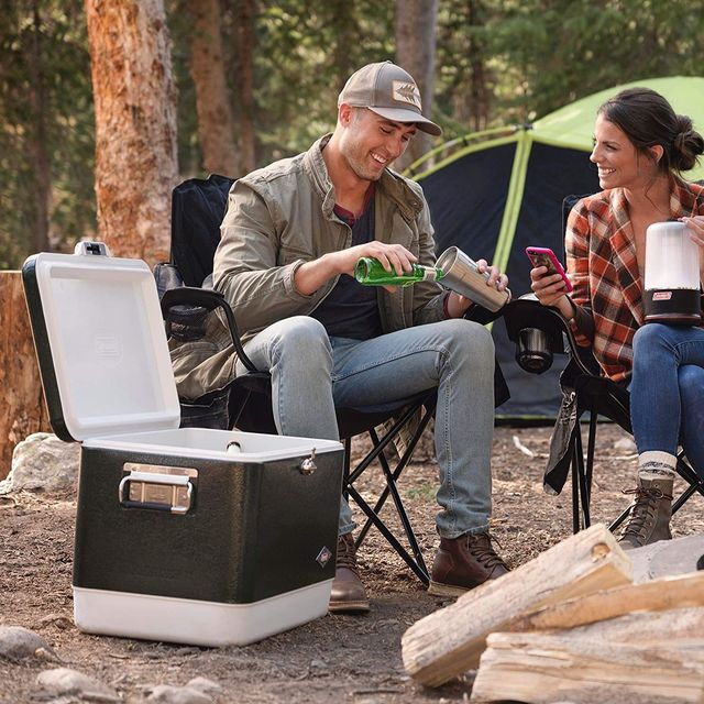 a campsite with a cooler, logs, a couple in camping chairs and a tent