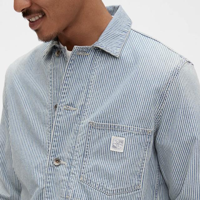 a model wearing a blue railroad stripe chore jacket